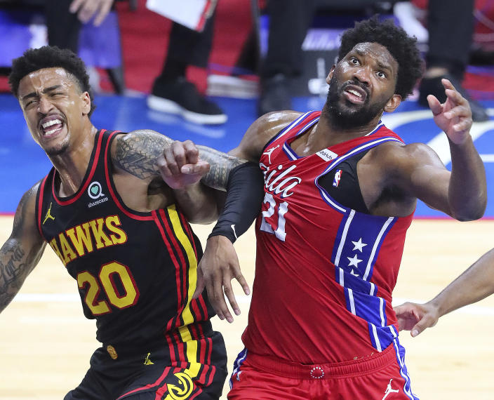 Atlanta Hawks forward John Collins, left, and Philadelphia 76ers center Joel Embiid, right, battle for a rebound under the basket in a NBA second round Eastern Conference playoff basketball game on Sunday, June 6, 2021, in Philadelphia. (Curtis Compton/Atlanta Journal-Constitution via AP)