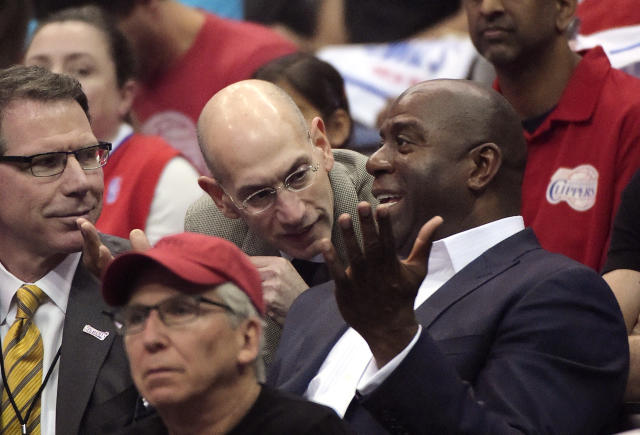 NBA Commissioner Adam Silver, center, talks with Magic Johnson, right, as Kiki Vandeweghe looks on as they watch the Los Angeles Clippers play the Oklahoma City Thunder in the first half of Game 4 of the Western Conference semifinal NBA basketball playoff series, Sunday, May 11, 2014, in Los Angeles. (AP Photo/Mark J. Terrill)