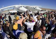 Guests try to photograph Richard Branson, standing in front of SpaceShipTwo, center, and WhiteKnightTwo, outside the new Spaceport America hangar.