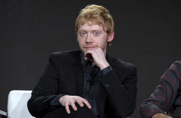 Rupert Grint sits onstage in black.