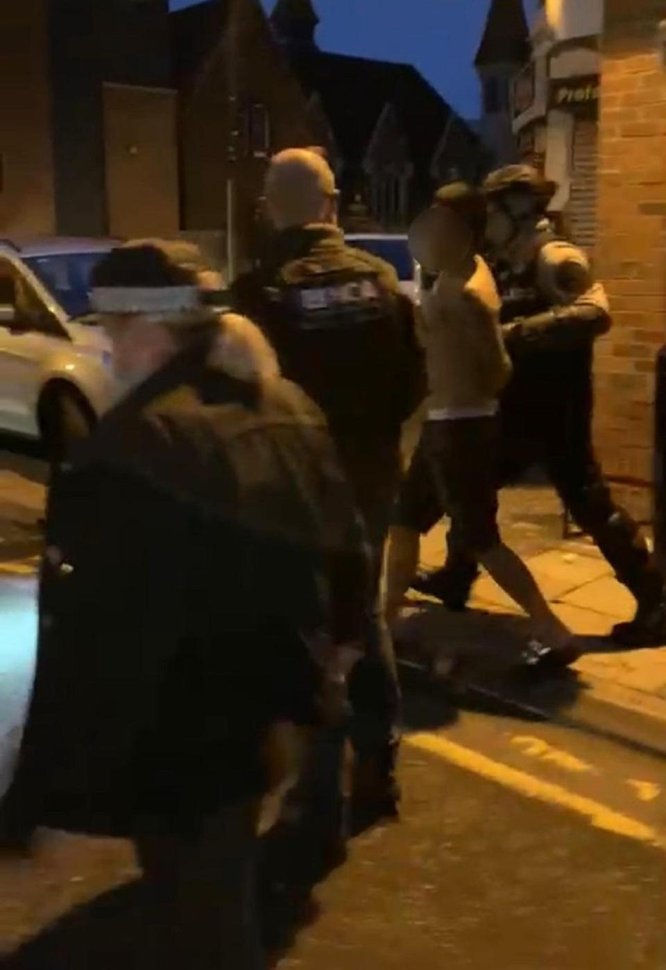 A suspect is lead away after the raid. Credit: National Crime Agency/PA