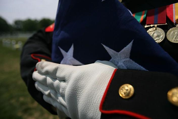 A folded national ensign is held carefully prior to the burial of Maj. Douglas A. Zembiec