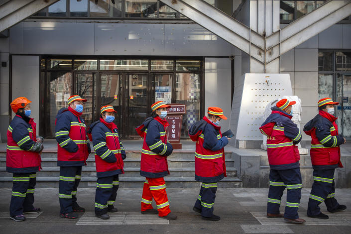Urban street cleaners wearing face masks to protect against the spread of the coronavirus line up for mass COVID-19 testing in a central district of Beijing, Friday, Jan. 22, 2021. Beijing has ordered fresh rounds of coronavirus testing for about 2 million people in the downtown area following new cases in the Chinese capital. (AP Photo/Mark Schiefelbein)