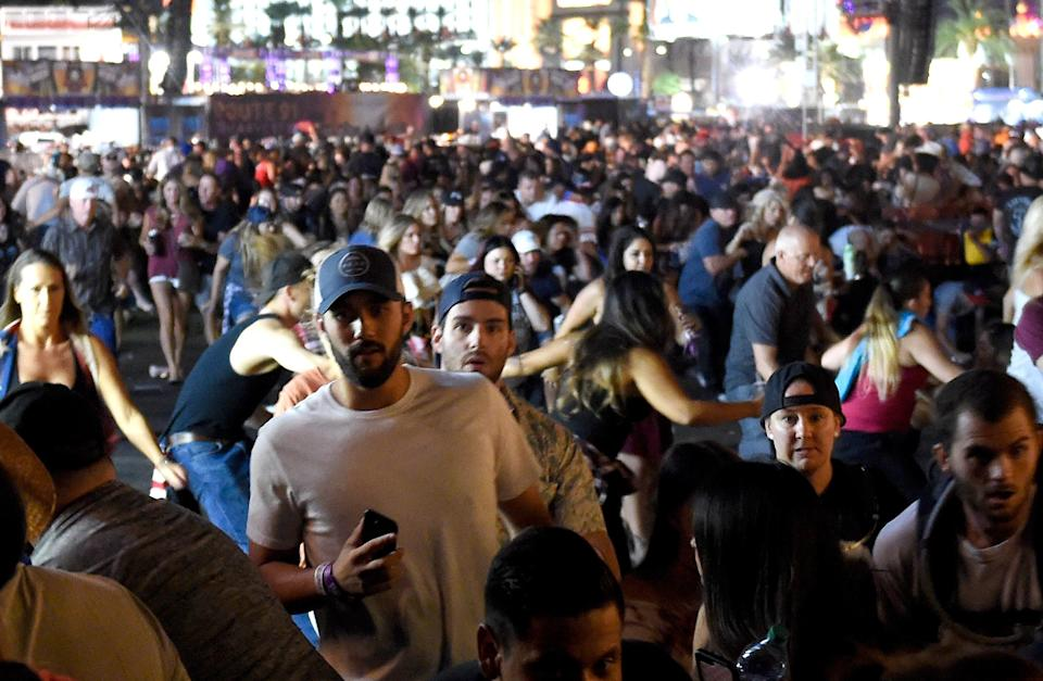 <p>People flee the Route 91 Harvest country music festival grounds. (Getty) </p>