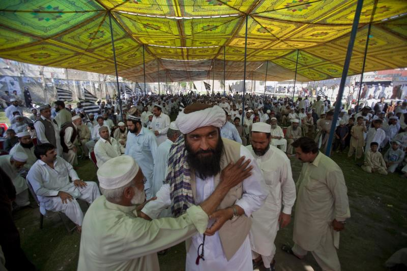 "In this Thursday, May 2, 2013 photo, Maulana Shujaul Mulk, center, pro-Taliban Jamiat-e-Ulema Islam (JUI-F), is greeted by a supporter as he arrive to address an election campaign rally in Mardan, Pakistan. Mulk is among several Pakistani Islamists and sectarian groups contesting for the country's upcoming parliamentary elections, which are divided and scattered though, they are still in a position to secure enough strength to play Pakistani establishment bid to ""hound"" the next frail government in influencing its decisions about the U.S. forces withdrawal from Afghanistan in 2014. (AP Photo/Anjum Naveed)"