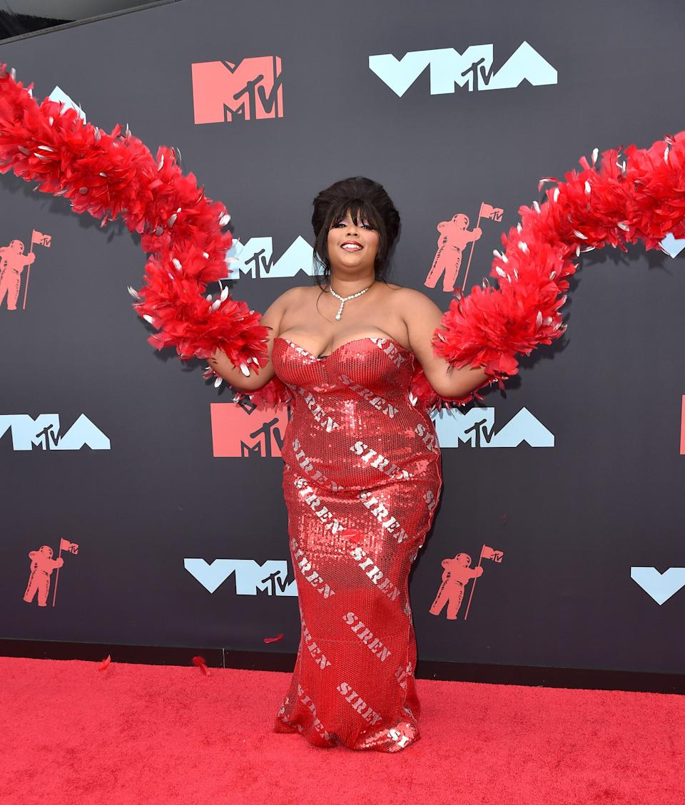 """Sound the alarm. It's always a treat to see what looks Lizzo will serve for the red carpet of a major awards show. The 2019 VMAs were an example of the singer's artistic expression with her fun """"siren"""" gown and matching boa – all by Moschin. Another round of applause for her fun '60s-inspired beehive updo."""