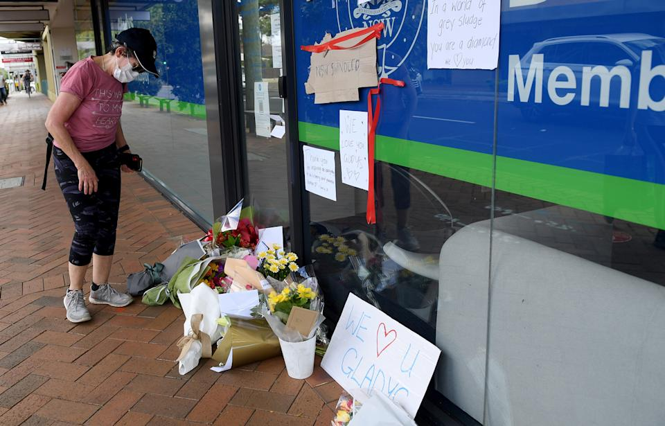 A person looks over the tributes building outside Gladys Berejiklian's Sydney electoral office.