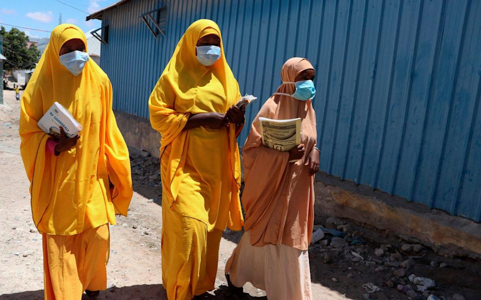 In this file photo taken on March 19, 2020 Students walk in a Mogadishu neighbourhood wearing face masks as a protective measure against the COVID-19 coronavirus. - Abdirazak Hussein Farah/AFP