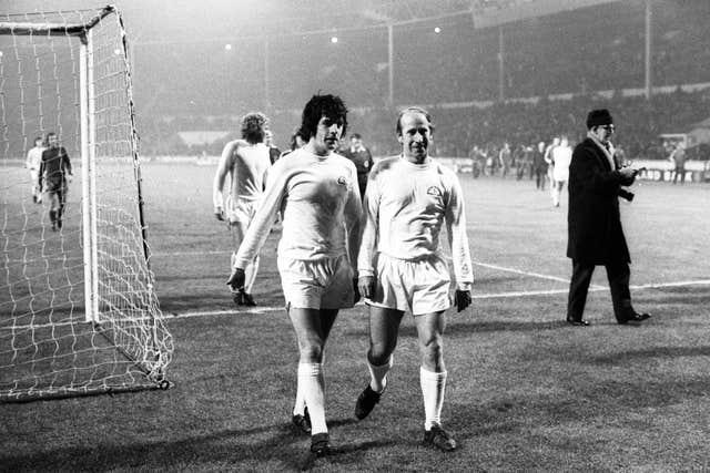 Peter Lorimer and Bobby Charlton walk off the pitch at Wembley after the British Three v the Common Market match in 1973