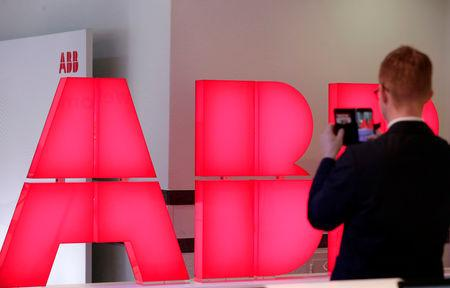 A man takes pictures of the logo of Swiss power technology and automation group ABB ahead of a news conference to present the company's full year results, in Zurich, Switzerland, February 8, 2018. REUTERS/Moritz Hager