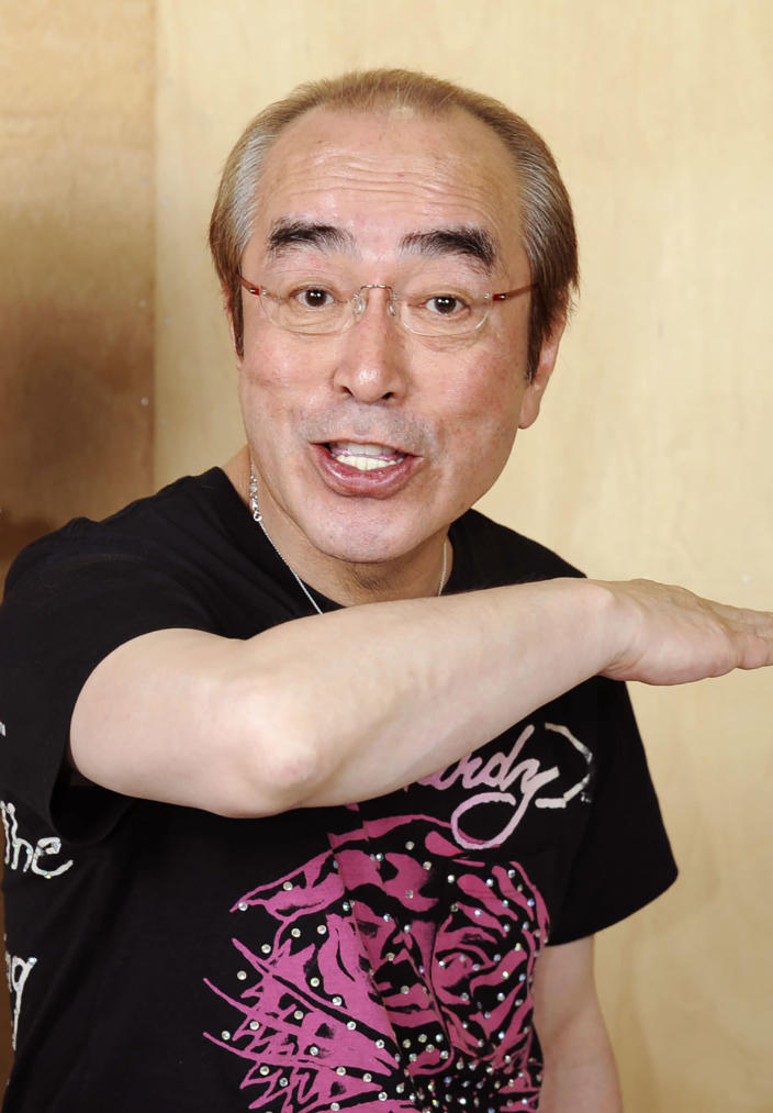 In this May 2012, photo, Japanese comedian Ken Shimura gestures with a funny face to a photographer in Tokyo. The nationally popular Japanese comedian, who said was drawing inspired from Jerry Lewis, has died of the COVID-19 pneumonia, a first known celebrity victim of the virus in Japan. He was 70. Shimura, who had fans of all generations with his slapstick jokes and funny faces, had been treated at a Tokyo hospital, died of the virus Sunday, March 29, 2020, his agency, Izawa Office, said. (Kyodo News via AP)