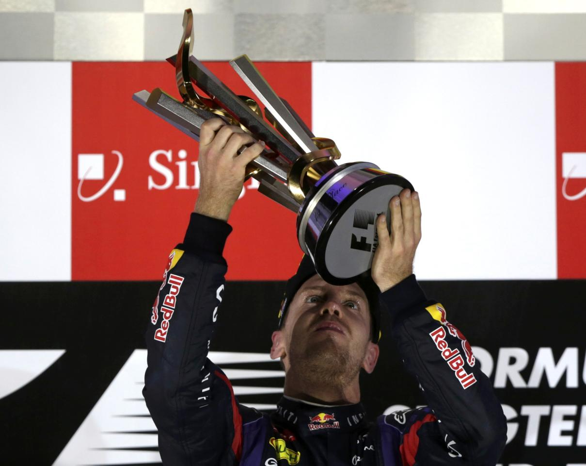 Red Bull Formula One driver Sebastian Vettel of Germany holds the trophy on the podium after winning the Singapore F1 Grand Prix at the Marina Bay street circuit in Singapore September 22, 2013. Vettel cruised to a third straight Singapore Grand Prix victory on Sunday and moved closer to a fourth consecutive Formula One world title with a dominant drive under the floodlights at the Marina Bay Street Circuit. REUTERS/Pablo Sanchez (SINGAPORE - Tags: SPORT MOTORSPORT F1)