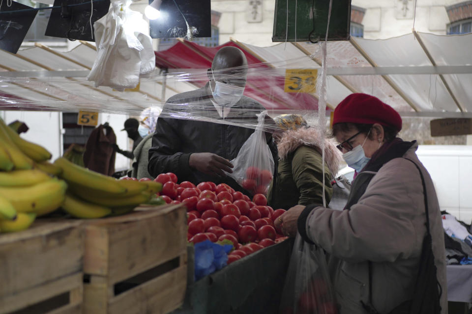 A woman wearing protective face masks as precaution against the conoravirus shops at an outdoor market in Paris, Friday, Oct. 30, 2020. France re-imposed a monthlong nationwide lockdown Friday aimed at slowing the spread of the virus, closing all non-essential business and forbidding people from going beyond one kilometer from their homes except to go to school or a few other essential reasons. (AP Photo/Thibault Camus)