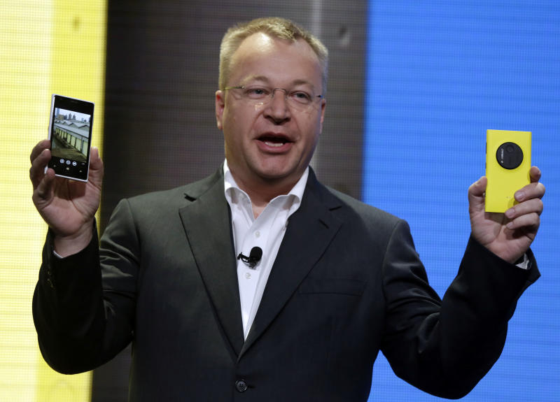 FILE - A Thursday, July 11, 2013 photo from files showing Nokia CEO Stephen Elop displaying his company's Nokia Lumia 1020, in New York. Struggling Nokia Corp. on Thursday said its sales continued to drop in the second quarter, while it managed to reduce its net loss amid continued cost-cuts. The Finnish cellphone maker said second-quarter sales fell to 5.7 billion euros ($7.49 billion) from 7.5 billion euros in the same period last year. Net loss for the April-June period was 227 million euros, compared to a net loss of 1.41 billion euros a year earlier. (AP Photo/Richard Drew, File)