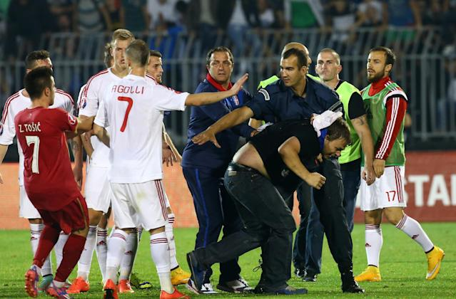 A policeman escorts a Serbian fan that invaded the pitch after a flag with Albanian national symbols was flown by a remotely operated drone during the UEFA Euro 2016 match between Serbia and Albania in Belgrade on October 14, 2014 (AFP Photo/Gen Shkullaku)
