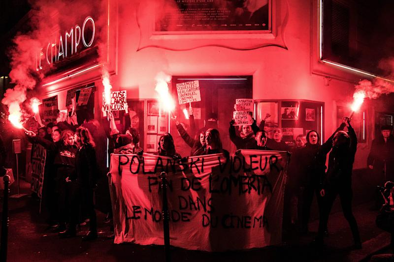 "Demonstrators hold banners reading ""Polanski rapist"" as they hold flares during a protest against French-Polish film director Roman Polanski outside the ""Champo"" cinema hall in Paris on November 12, 2019. - Interviews to promote Polanski's new film ""An Officer and a Spy"" have been either cancelled or pulled after a new rape allegation against the controversial director on November 8. (Photo by Christophe ARCHAMBAULT / AFP) (Photo by CHRISTOPHE ARCHAMBAULT/AFP via Getty Images)"