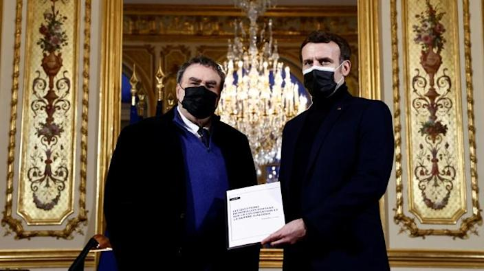 French President Emmanuel Macron (R) poses with French historian Benjamin Stora for the delivery of a report on the colonisation and the Algerian War