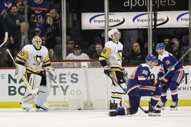Pittsburgh Penguins goaltender Matt Murray (30) watches as New York Islanders' Brock Nelson (29) celebrates with Derick Brassard (10) after Nelson scored during the third period of an NHL hockey game Thursday, Nov. 21, 2019, in New York. The Islanders won 4-3 in overtime. (AP Photo/Frank Franklin II)