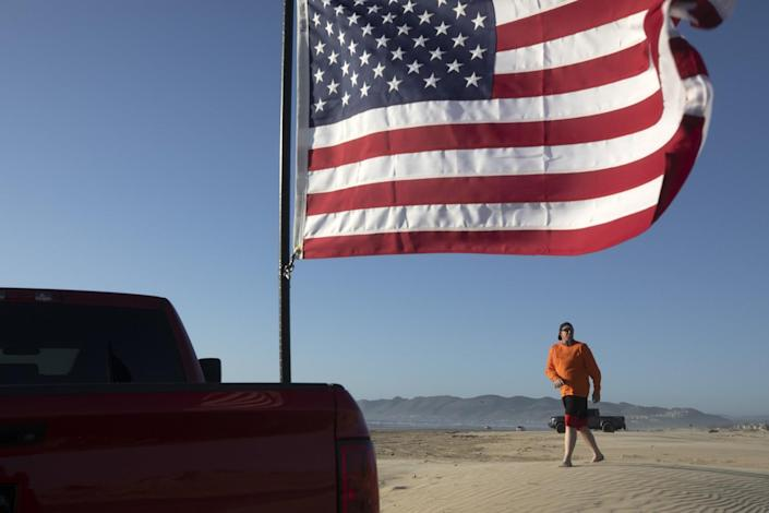 An American flag with a person in the background