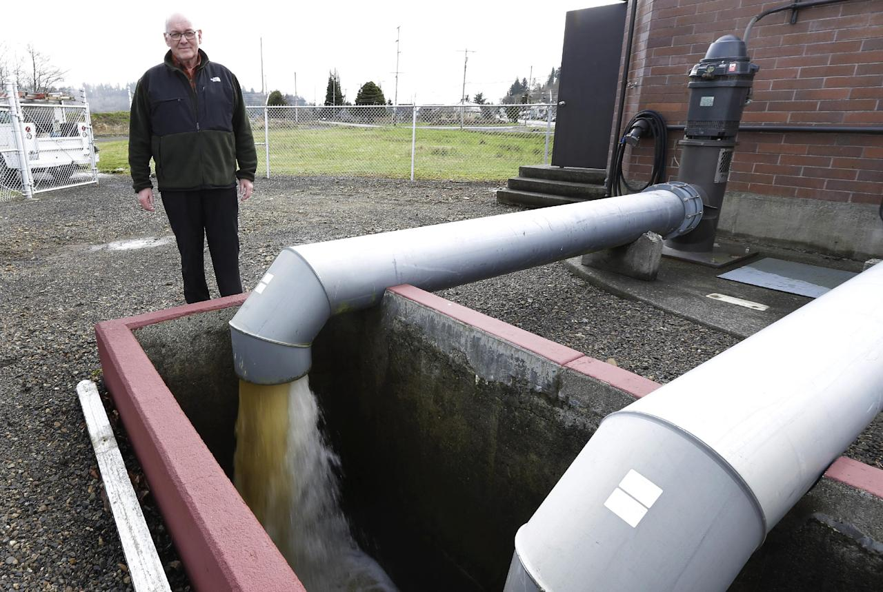 Jack Durney, mayor of Hoquiam, Wash., stands Monday, March 18, 2014 next to a pump that takes groundwater away from neighborhoods in his town, most of which is located on a flood plain. Durney says possible increases in federal flood insurance rates would adversely affect many who live in Hoquiam. (AP Photo/Ted S. Warren)