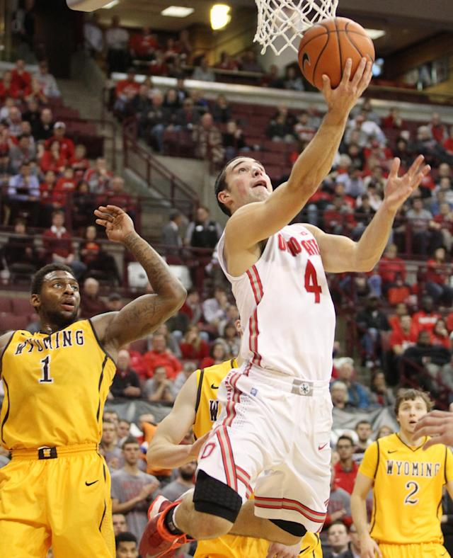Ohio State's Aaron Craft (4) scores under the basket as Wyoming's Charles Hankerson (1) watches during the second half of an NCAA college basketball game, Monday, Nov. 25, 2013, in Columbus, Ohio. (AP Photo/Mike Munden)