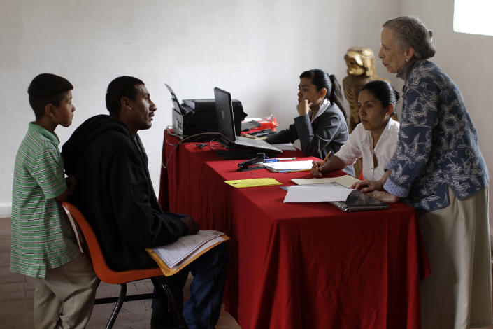 """In this Tuesday, July 10, 2012, Rogelio Hernandez Sanchez, 34, second from left, and his son, Rogelio Hernandez Medina, 7, left, listen to Ellen Calmus, right, a coordinator of the """"Proyecto El Rincon"""" or """"The Corner Project"""", a local non-profit organization for migrant families, as he tries to get his son's U.S. birth certificate stamped by Mexican authorities in Malinalco, Mexico. Because of the Byzantine rules of Mexican and U.S. bureaucracies, tens of thousands of U.S. born children of Mexican migrant parents now find themselves without access to basic services in Mexico - unable to officially register in school or sign up for health care at public hospitals and clinics that give free check-ups and medicines.(AP Photo/Dario Lopez-Mills)"""