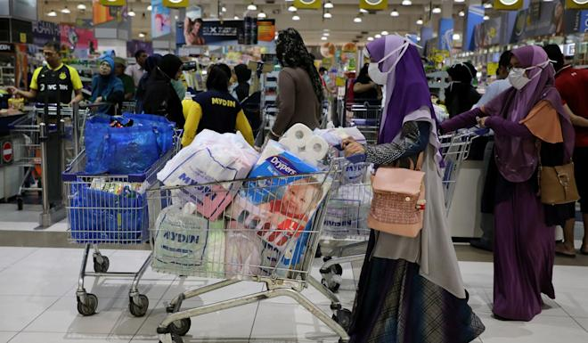 Shoppers wearing protective masks pictured in a supermarket in Malaysia on Tuesday, amid fears of disruption after the government-ordered partial lockdown. Photo: Reuters