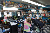 Musical memorabilia line the walls and shelves of the Glory Days Corner Barber Shop as Katie Hennenfent, left, cuts Ryan Hardwell's hair and as Sam Carr, right, attends to Jack Dechow in Galesburg, Ill., Wednesday, June 16, 2021. (AP Photo/Shafkat Anowar)