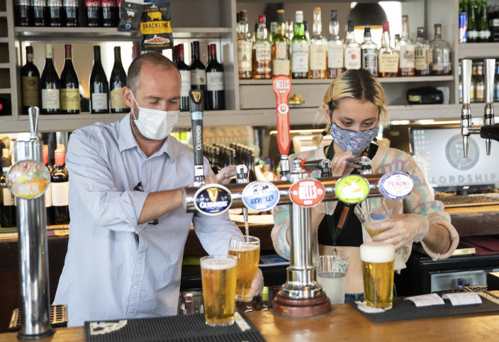 Employees pull pints at the Lordship pub in East Dulwich. The UK Government announced that Pubs, Hotels and Restaurants can open from Saturday, July 4 providing they follow guidelines on social distancing and sanitising. Photo: John Phillips/Getty Images