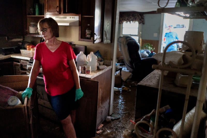 Jaquita Buchanan works on salvaging items from her mother's home after flooding in Waverly, Tennessee