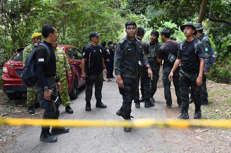 Members of a rescue team are seen behind a police line at the Dusun Resort (AFP/Getty Images)