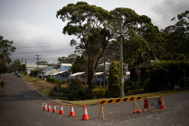 A road block is seen on a crossroad next to houses in Hyams Beach