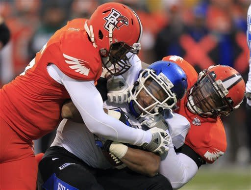 Buffalo running back Devin Campbell, center, is tackled by Bowling Green's Charlie Walker, left, and Bryan Thomas during the fourth quarter of an NCAA college football game Friday, Nov. 23, 2012, in Columbus, Ohio. Bowling Green beat Buffalo 21-7. (AP Photo/Jay LaPrete)