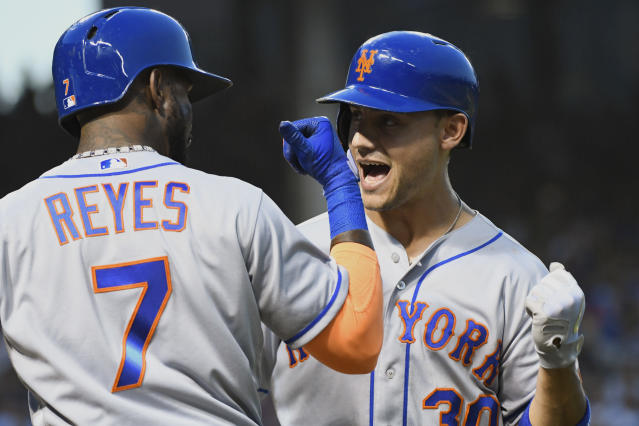 New York Mets' Michael Conforto (30) celebrates with Jose Reyes (7) after hitting a home run against the Chicago Cubs during the second inning of a baseball game on Monday, Aug. 27, 2018, in Chicago. (AP Photo/Matt Marton)