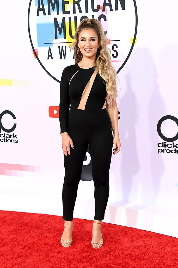 <p>Country singer Jessie James Decker opted for pants over a dress, by way of a black jumpsuit with strategically placed cut-outs, and she looked pretty happy with her choice. (Photo: Jon Kopaloff/FilmMagic) </p>