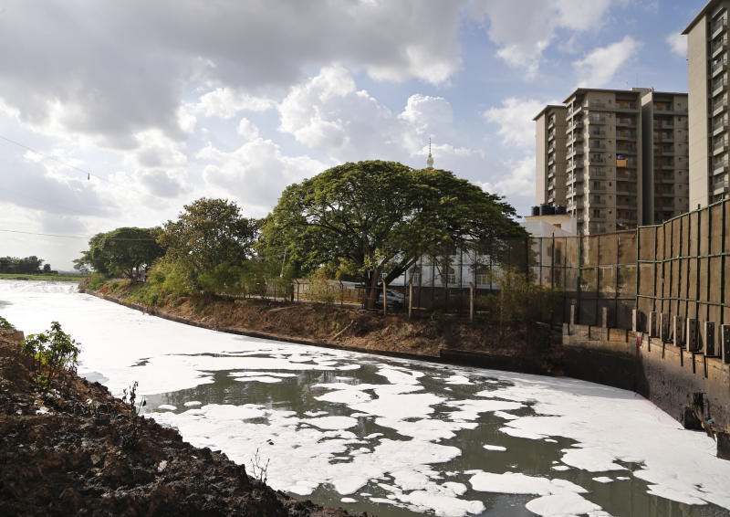 FILE - In this June 5, 2017, file photo, toxic froth from industrial pollution floats on Bellundur Lake on World Environment Day, in Bangalore, India. Environmental pollution - from filthy air to contaminated water - is killing more people every year than all war and violence in the world. (AP Photo/Aijaz Rahi, File)