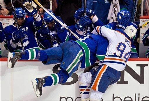 Edmonton Oilers' Ryan Smyth, right, checks Vancouver Canucks' Kevin Bieksa into the Vancouver bench during the second period of an NHL hockey game in Vancouver, British Columbia, on Tuesday, Jan. 24, 2012. (AP Photo/The Canadian Press, Darryl Dyck)