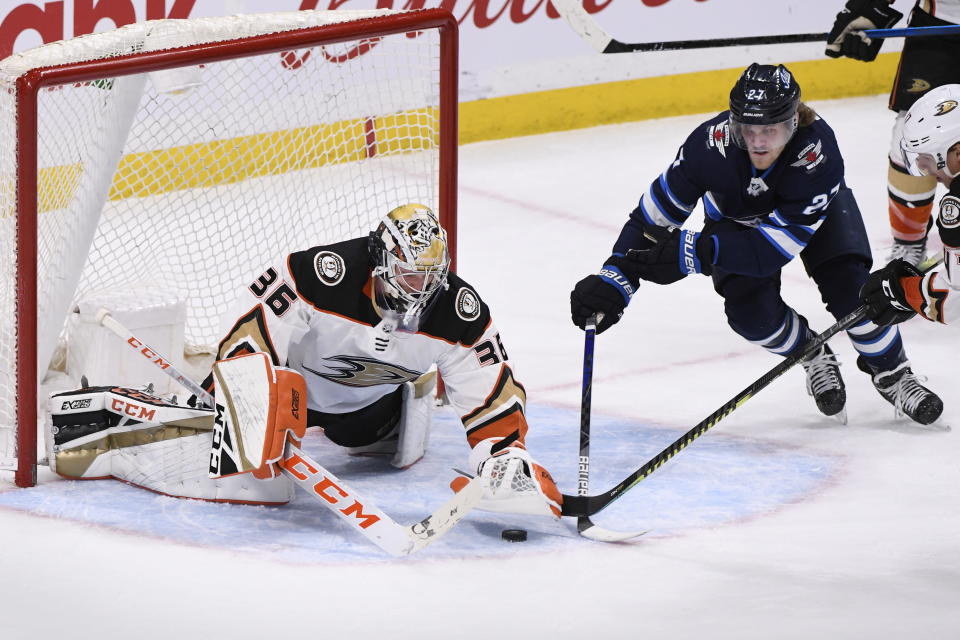 Anaheim Ducks' goaltender John Gibson (36) covers up the puck as Winnipeg Jets' Nikolaj Ehlers (27) looks for the rebound during the third period of an NHL hockey game, Sunday, Dec. 8, 2019 in Winnipeg, Manitoba. (Fred Greenslade/The Canadian Press via AP)