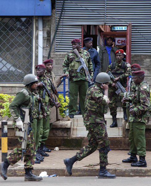 Kenya security personnel move to their positions as others stand guard outside a shopping mall in Nairobi, Kenya, Sunday, Sept. 22, 2013. Kenya authorities said Islamic extremist attackers remain inside the upscale Kenyan shopping mall, holding an unknown number of hostages, after killing at least 39 and injuring 150 during the Saturday's attack. (AP Photo/Sayyid Azim)