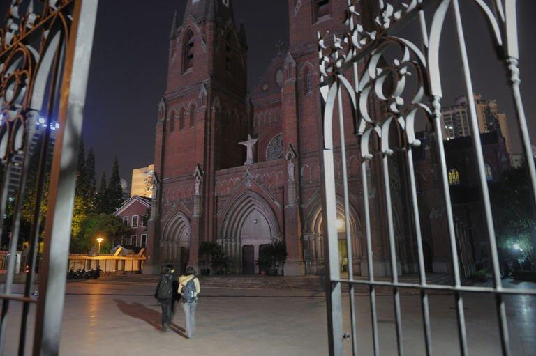 Two people walk into the grounds of the St Ignatius Cathedral in Shanghai in the evening on April 27, 2013