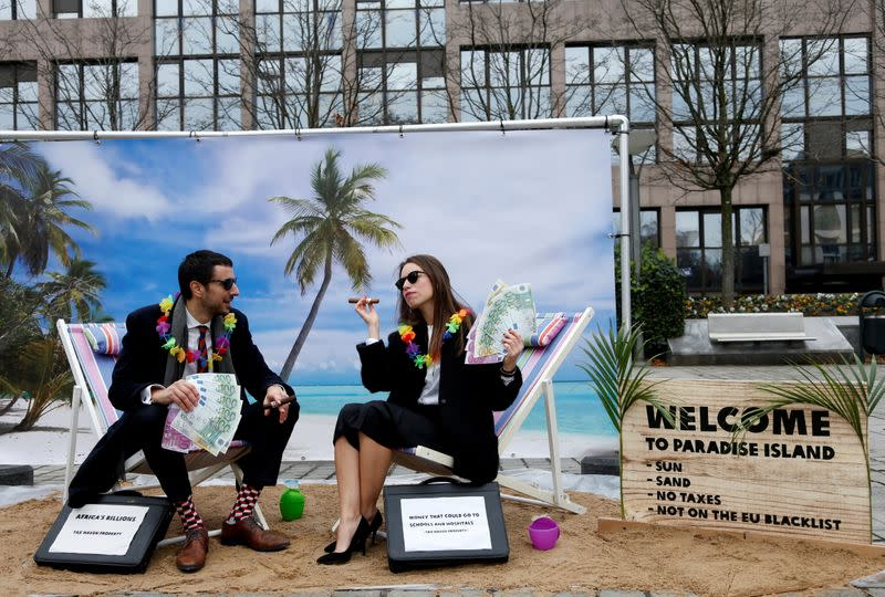 FILE PHOTO: Activists stage a protest on a mock tropical island beach representing a tax haven outside a meeting of European Union finance ministers in Brussels