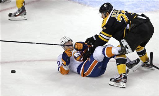 Boston Bruins center Chris Kelly, right, drops New York Islanders center Keith Aucoin to the ice while chasing the puck during the first period of an NHL hockey game, Thursday, April 11, 2013, in Boston. (AP Photo/Charles Krupa)