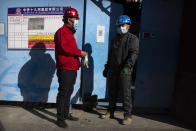 Workers wearing face masks to protect against the coronavirus stand outside of a construction site in Beijing, Thursday, Oct. 22, 2020. The number of confirmed COVID-19 cases across the planet has surpassed 40 million, but experts say that is only the tip of the iceberg when it comes to the true impact of the pandemic that has upended life and work around the world. (AP Photo/Mark Schiefelbein)