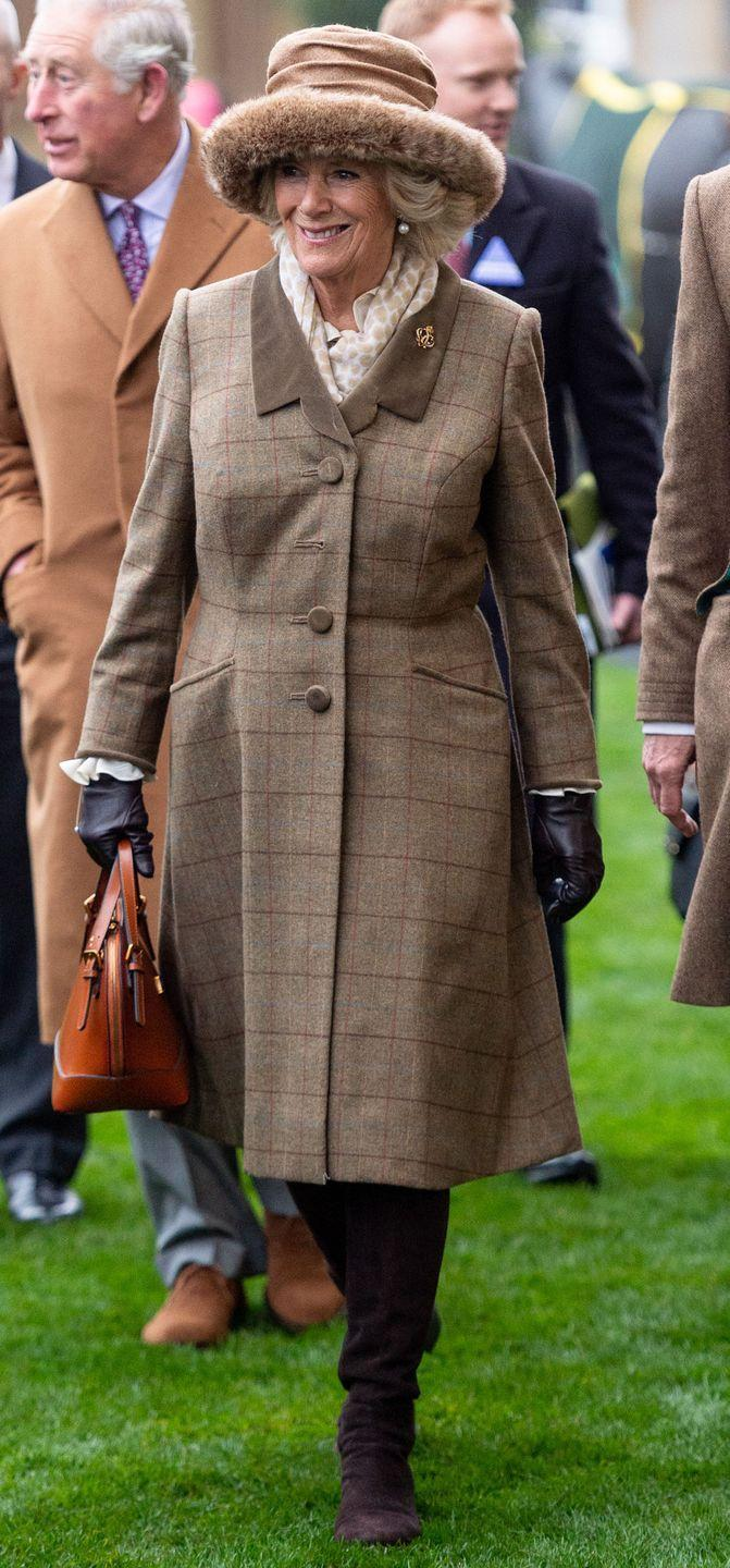 <p>The Duchess of Cornwall looked smart in a tweed coat, brown boots, and a fur lined hat to attend the Prince's Countryside Fund Racing Weekend at Ascot Racecourse. The duchess finished the look with a beige polka dot scarf, brown gloves, and a camel colored bag. </p>