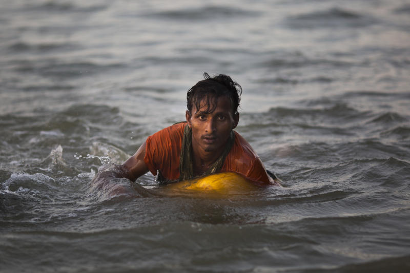 In this Nov. 4, 2017, file photo, Rohingya Muslim Abdul Karim, 19, uses a yellow plastic oil container as a flotation device as he swims the Naf river while crossing the Myanmar-Bangladesh border in Shah Porir Dwip, Bangladesh. Rohingya Muslims escaping the violence in their homeland of Myanmar are now so desperate that some are swimming to safety in neighboring Bangladesh, even if they have never been in the water before. (AP Photo/Bernat Armangue, File)