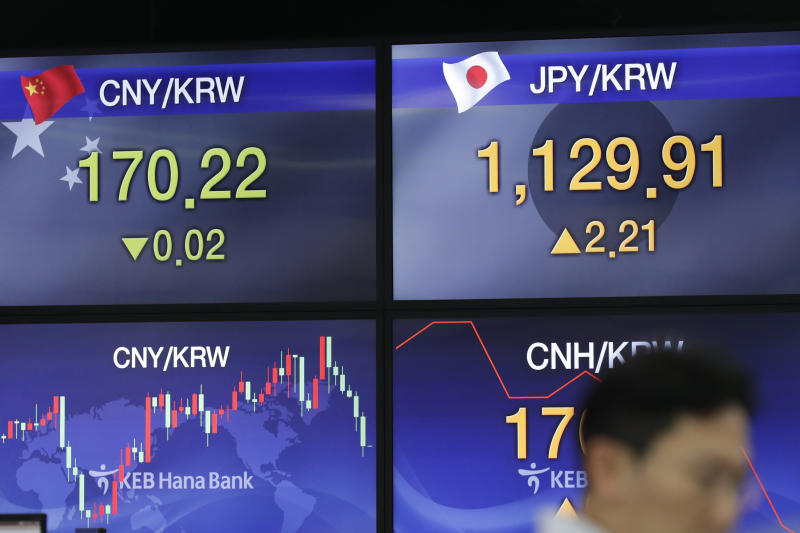 A currency trader walks near screens showing the foreign exchange rates at the foreign exchange dealing room in Seoul, South Korea, Thursday, Aug. 22, 2019. Asian stock markets are mixed Thursday following Wall Street's rebound as investors looked ahead to a speech by the U.S. Federal Reserve chairman for clues about possible interest rate cuts. (AP Photo/Lee Jin-man)