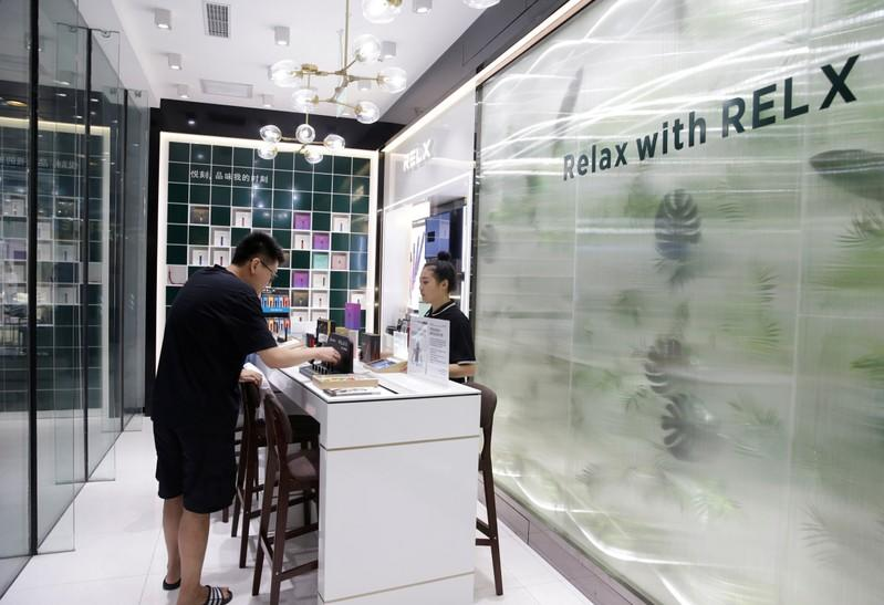 A customer selects the Relx e-cigarettes at its flagship store in Beijing