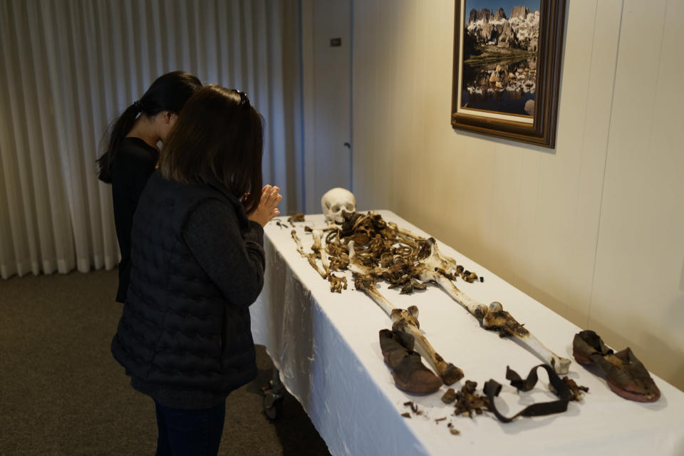 Lori Matsumura, foreground, and her niece, Lilah Matsumura, pray for their ancestor, Giichi Matsumura, at Brune Mortuary in Bishop, Calif., Monday, Feb. 17, 2020. Giichi Matsumura was a prisoner at the Manzanar internment camp during World War II and died on a hike in the Sierra in the waning days of the war in August 1945. Hikers discovered his mountainside grave and unearthed the skeleton in 2019, leading authorities to retrieve the bones and return them to the Matsumura family. (AP Photo/Brian Melley)