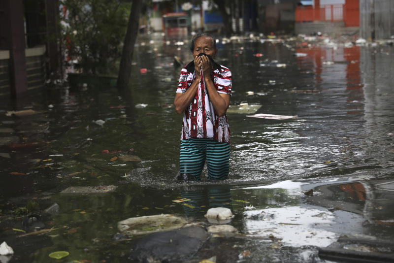 A woman reacts as she wades flood water in Jakarta, Indonesia, Saturday, Jan. 4, 2020. Monsoon rains and rising rivers submerged parts of greater Jakarta and caused landslides in Bogor and Depok districts on the city's outskirts as well as in neighboring Lebak, which buried a number of people. (AP Photo/Dita Alangkara)
