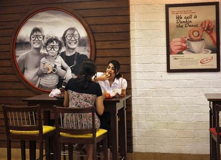 Customers eat at a Dunkin' Donuts store in New Delhi